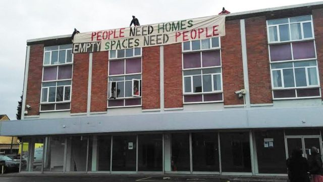 """Layla Moran calls for City Council to """"step up"""". Image: Oxford residents and local homeless people dropping an enormous banner from the front of the old VW garage on Iffley Road in January 2017."""
